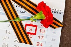 Helle rote Gartennelke eingewickelt mit George-Band, das auf dem Kalender mit gestaltetem am 9. Mai Datum - Victory Day-Grußkarte Lizenzfreies Stockfoto