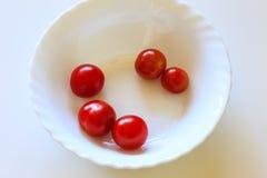 Helle rote Kirschtomaten in einer weißen Schüssel Stockfotografie