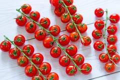 Helle rote Kirschtomaten am weißen Holztisch stockbild