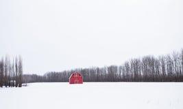 Helle rote Scheune in der Winterlandschaft Lizenzfreie Stockfotografie