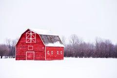 Helle rote Scheune in der Winterlandschaft Stockbilder