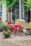Helle rote Stühle vor einem historischen niederländischen Haus Stockbilder