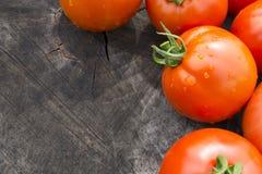 Helle rote Tomaten auf einem strukturierten hölzernen Hintergrund Lizenzfreies Stockfoto