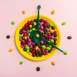 Helle Süßigkeitsdragées auf einer gelben Platte mit grünen Löffeln lizenzfreie stockfotografie
