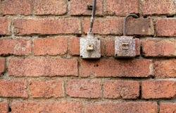 Helle Schalter auf Backsteinmauer Stockfotografie