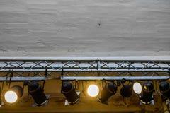 Helle Scheinwerfer, die von der Wand hängen Große graue Wand mit Mann Stockfotografie
