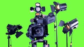 Helle Scheinwerfer stehen nahe Berufsvideokamera auf einem grünen Schirm stock footage