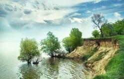 Helle Sommerlandschaft - eine steile Klippe durch den Fluss Lizenzfreie Stockfotos