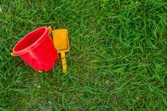 Helle Spielwaren Spachtel und Eimer, die auf dem grünen Gras liegen sie spielten ein Kind stockbild