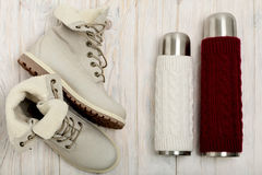 Helle Stiefel des Winters und eine Thermosflasche in der gestrickten Abdeckung auf dem bri Lizenzfreies Stockfoto