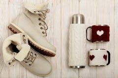 Helle Stiefel des Winters und eine Thermosflasche in der gestrickten Abdeckung auf dem bri Stockfoto