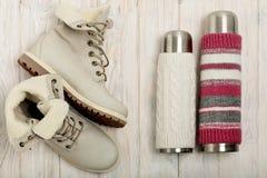 Helle Stiefel des Winters und eine Thermosflasche in der gestrickten Abdeckung auf dem bri Stockfotos