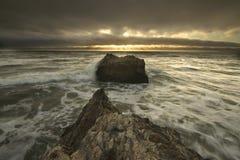 Helle Strahlen über den Meereswogen, die auf Felsen spritzen Stockfoto