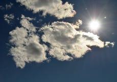 Helle Strahlen der Sonne geben eine ungewöhnliche Farbe zu den weißen flaumigen Wolken im dunkelblauen Himmel Lizenzfreies Stockbild