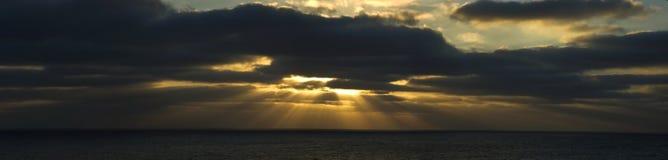 Helle Strahlen durch Wolken Stockfoto
