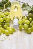 Helle Trauben mit Flasche Weißwein und Weinblättern auf einem weißen hölzernen Hintergrund, Abschluss oben Stockbilder
