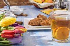 Helle Tulpen, Tee mit Zitrone, Gebäck auf einer weißen Platte Lizenzfreies Stockfoto