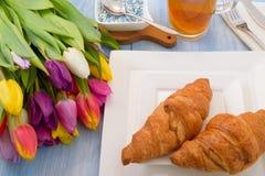 Helle Tulpen, Tee mit Zitrone, Gebäck auf einer weißen Platte Lizenzfreie Stockfotos