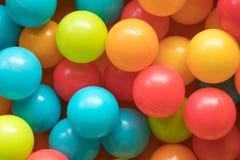 Helle und bunte Plastikspielzeugbälle, Ballgrube, Abschluss oben Stockfotos