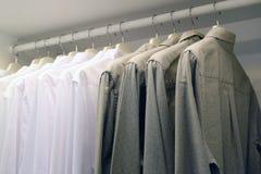 Helle und dunkle Hemden im Wandschrank auf dem Aufhänger stockfoto
