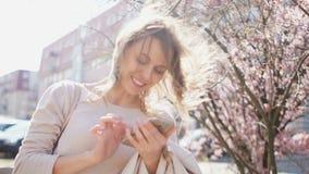 Helle und nette Stadtstraße der Frau im Frühjahr mit einem Smartphone in der Hand Nahes Portrait stock video
