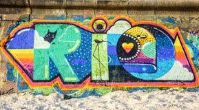 Helle und saftige Graffiti des Wortes RIO auf der Wand am sonnigen Tag in Ipanema setzen auf den Strand Stockfotos