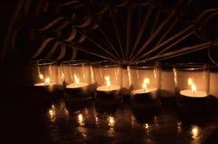 5 helle votive Kerzen des Tees in der Klarglaseisengießerei hinten Stockfotos