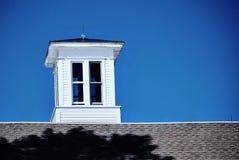 Helle weiße Kuppel sitzt auf Scheunendach gegen einen tiefen blauen Himmel Stockbild