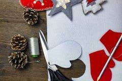 Helle Weihnachtsspielwaren hergestellt vom Filz Scheren, Bleistift, Thread und Stöße auf einem Holztisch Stockfotografie