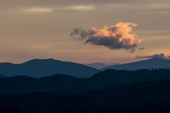 Helle Wolke hängt über Gebirgsrücken Stockfotos