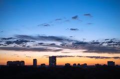 Helle Wolken im Abendhimmel vor dem hintergrund des Hochhauses Lizenzfreie Stockfotos