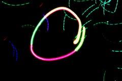 Heller abstrakter bunter pixelated Kreis des Neonlichtes auf einem schwarzen Hintergrund und andere farbige abstrakte Linien und  Lizenzfreies Stockbild