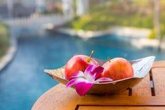 Heller Apfel mit Orchidee in der Platte auf dem Tisch lizenzfreie stockfotografie
