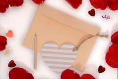 Heller Aprikosenumschlag, Herzkarte und Bleistift auf Hintergrund der weißen und rosafarbenen Blumenblätter Lizenzfreies Stockbild