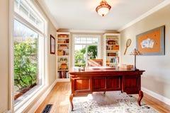 Heller Büroraum mit klassischem Schreibtisch und eingebauten Regalen Stockfotografie