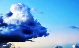 Heller blauer Himmel des Hintergrundes mit einer dunklen Sturmwolke Lizenzfreies Stockbild