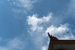 Heller blauer Himmel mit einigen Kumulus- und Altkumuluswolken, verziert mit typischen Balinesehausverzierungen stockfotografie
