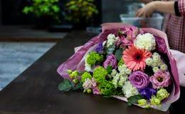 Heller Blumenstrauß von frischen Blumen auf einem braunen Holztisch stockfoto