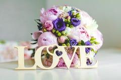 Heller Brautblumenstrauß von rosa und weißen Pfingstrosen mit einer hölzernen Tablette der Liebe liegt auf dem Tisch Schildliebe Lizenzfreies Stockfoto