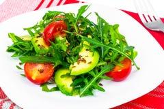 Heller diätetischer Salat vom Arugula, von der Avocado, von den tomates und vom Leinsamen Lizenzfreies Stockfoto