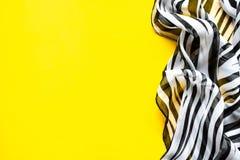Heller eleganter transparenter Gasschal mit Schwarzweiss-Streifen mit einem Gelbfarbhintergrund Draufsicht der Zebraverzierung Lizenzfreie Stockbilder