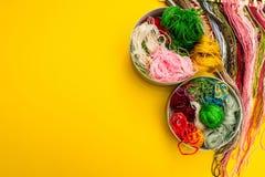 Heller farbiger Faden für das Stricken in einem Kasten auf einem gelben Hintergrund stockbild