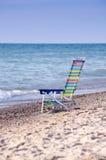 Heller farbiger Stuhl auf dem Strand Stockfotos