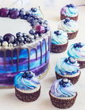 Heller festlicher blauer Kuchen mit Beeren und Schokolade und kleine Kuchen mit Sahne Lizenzfreies Stockbild