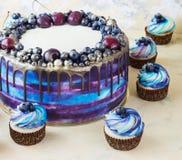 Heller festlicher blauer Kuchen mit Beeren und Schokolade und kleine Kuchen mit Sahne Stockfotos