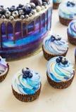 Heller festlicher blauer Kuchen mit Beeren und Schokolade und kleine Kuchen mit Sahne Lizenzfreie Stockfotos