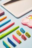Heller Gummi, Bleistiftspitzer und Stifte auf einer blauen Tabelle lizenzfreie stockbilder