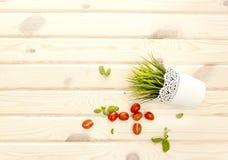 Heller hölzerner Hintergrund Basilikum und Tomaten stockbild