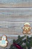 Heller hölzerner schäbiger Hintergrund mit Lebkuchenplätzchen und -Fichtenzweigen Lizenzfreies Stockfoto