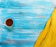Heller Hintergrund mit blaue, blaue gemalt Farbenbretter, ein Becher Tee und eine gelbe Strickjacke mit Kopienraum Beschneidungsp Stockbild